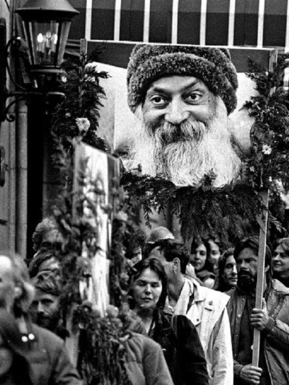 Followers of the Bhagwan Shree Rajneesh, some carrying posters of the guru, protest in Portland, Ore., in 1985 against his arrest. (Jack Smith / Associated Press)