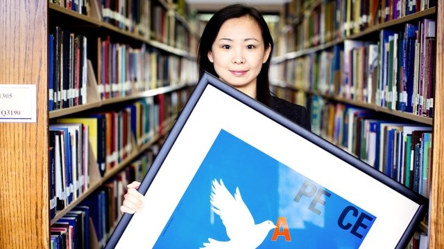 "A young woman holds a poster that says ""Peace"" with a white dove on a blue background."