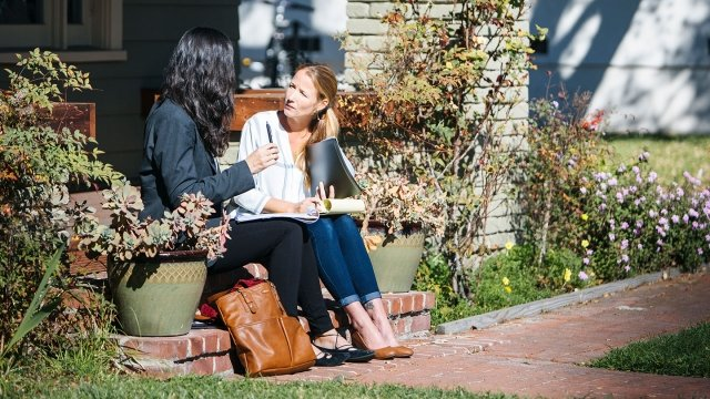 Two young women sit outside deep in discussion.