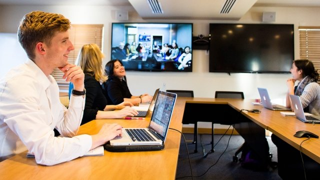 Four students in a classroom video conferencing with other students who appear on a large screen mounted to the wall.
