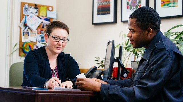 A student and career advisor work together in an office setting at a desk.