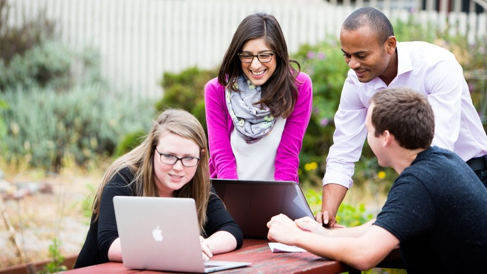 Students around a table outside look at their computers.