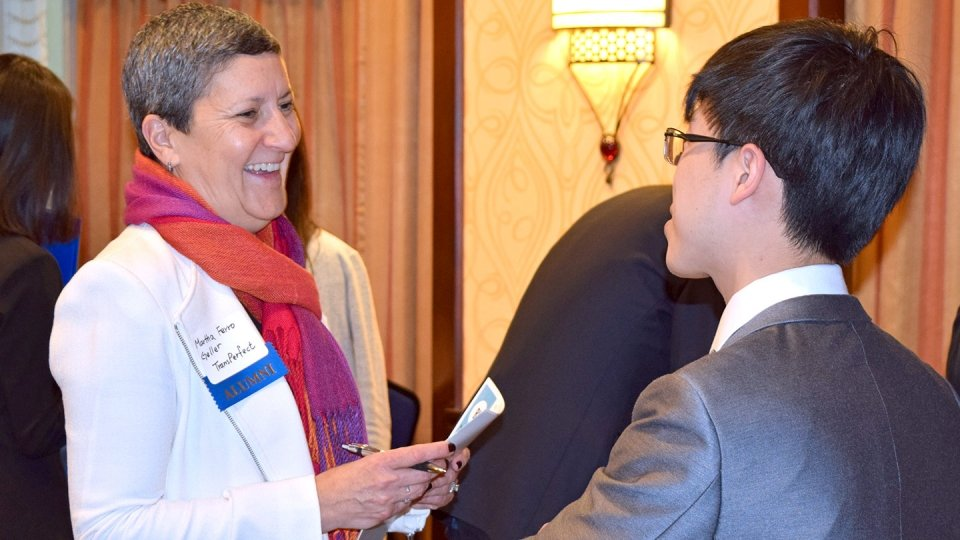 A student greets an alumna mentor at a career fair.