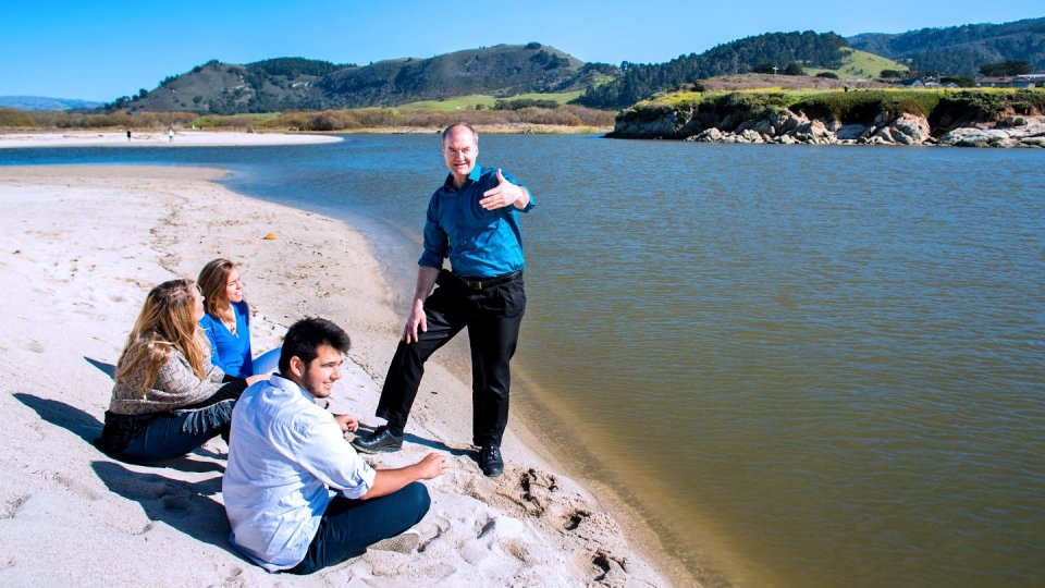 A professor and several students discuss sustainability issues along the shoreline at a beach in Monterey Bay.