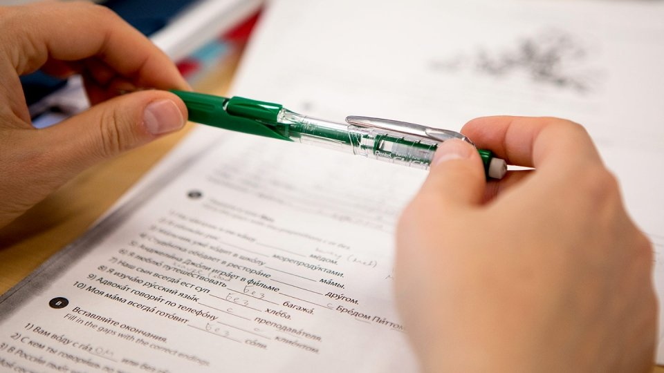 A student's green pen is poised over the Language Placement Test.