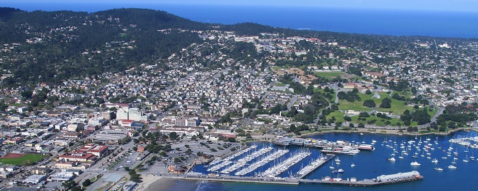 An aerial view of the Monterey Bay including boat harbor, city and hills, with view to the Pacific Ocean beyond
