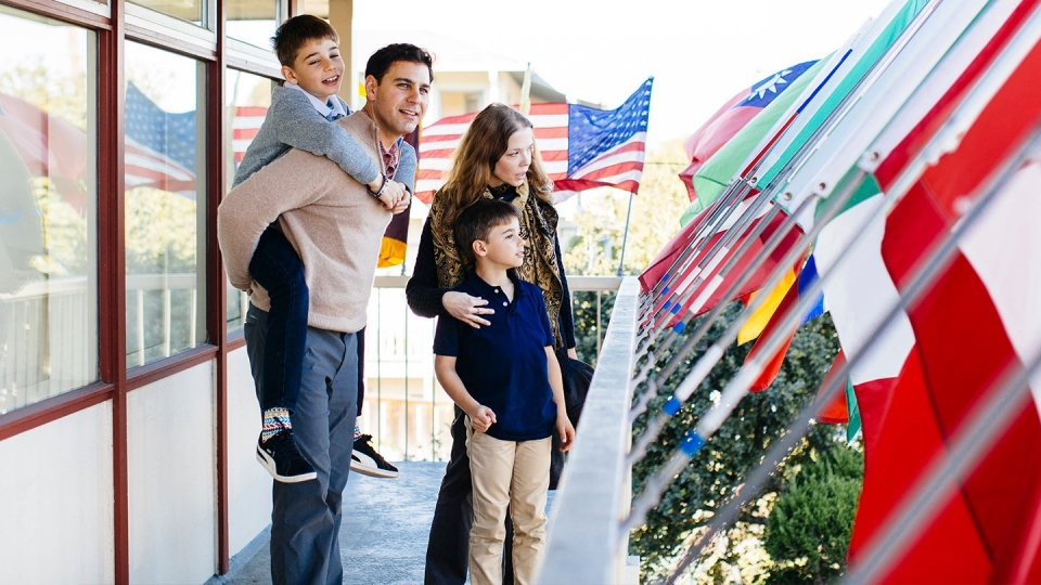 A father, mother and two sons stand on a blacony among world flags.