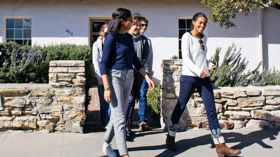Five students walking together on campus.
