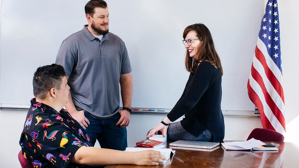 Two male students and a female student talk in a classroom.