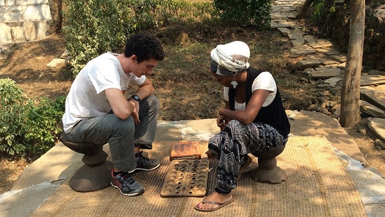 A Frontier Market Scouts Fellow plays the marble game mancala with a younger student.