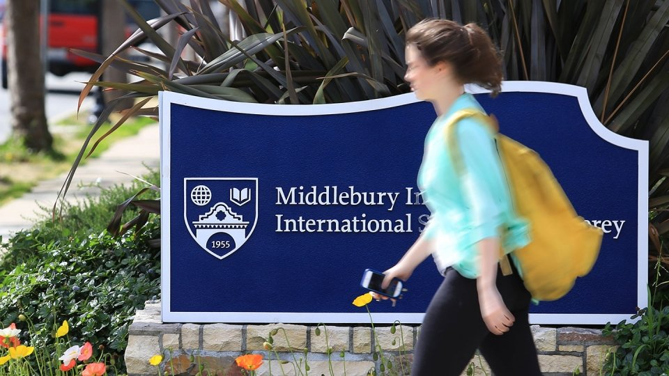 A young female student walks on campus in front of an Institute sign.
