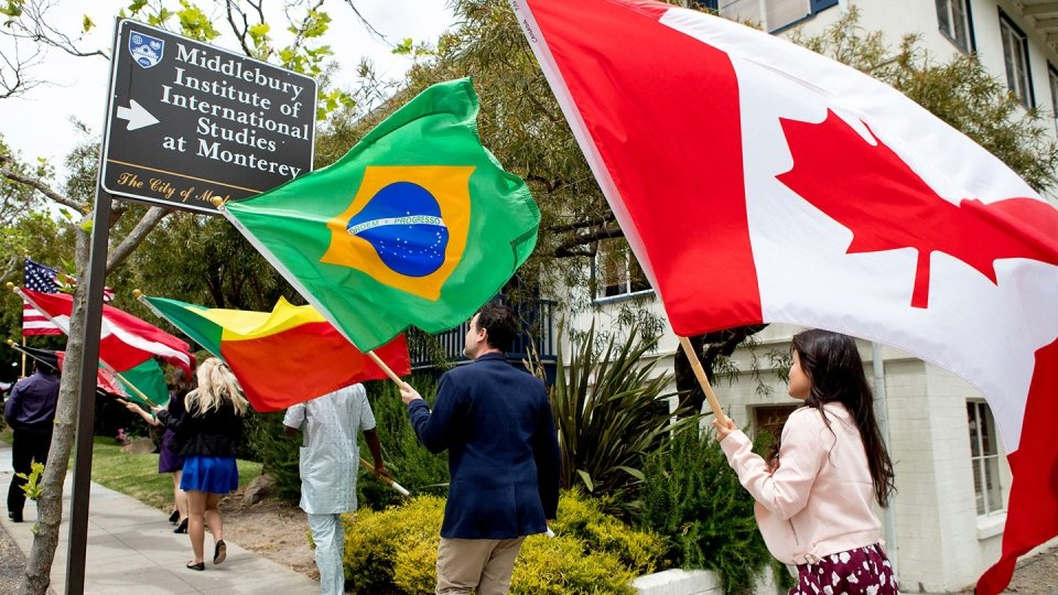 Students walking through campus holding flags from various countries.