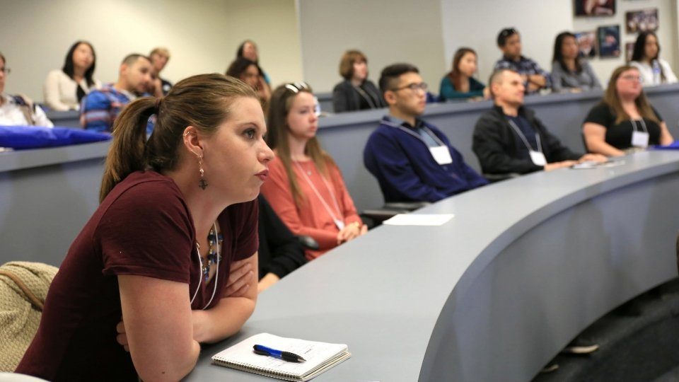 Student listens to professor in a seminar room.