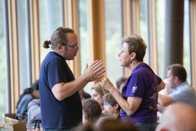 Two Hebrew Lifelong Learners have a discussion in crowded dining hall.