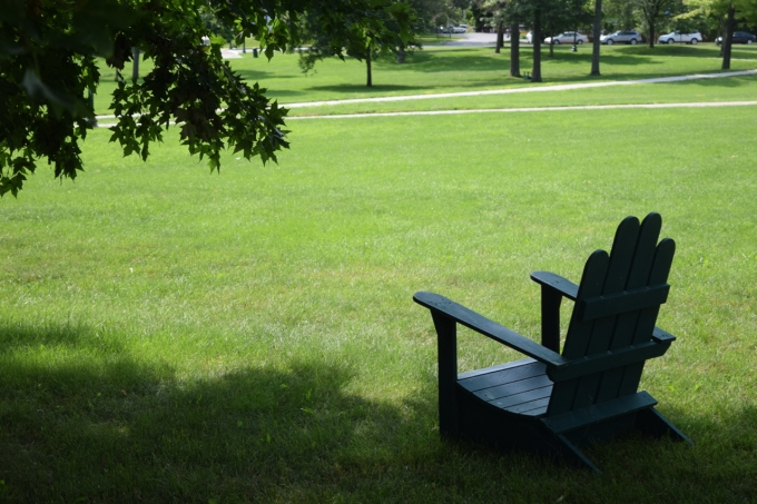 View of campus lawn with Adirondack chair on it.