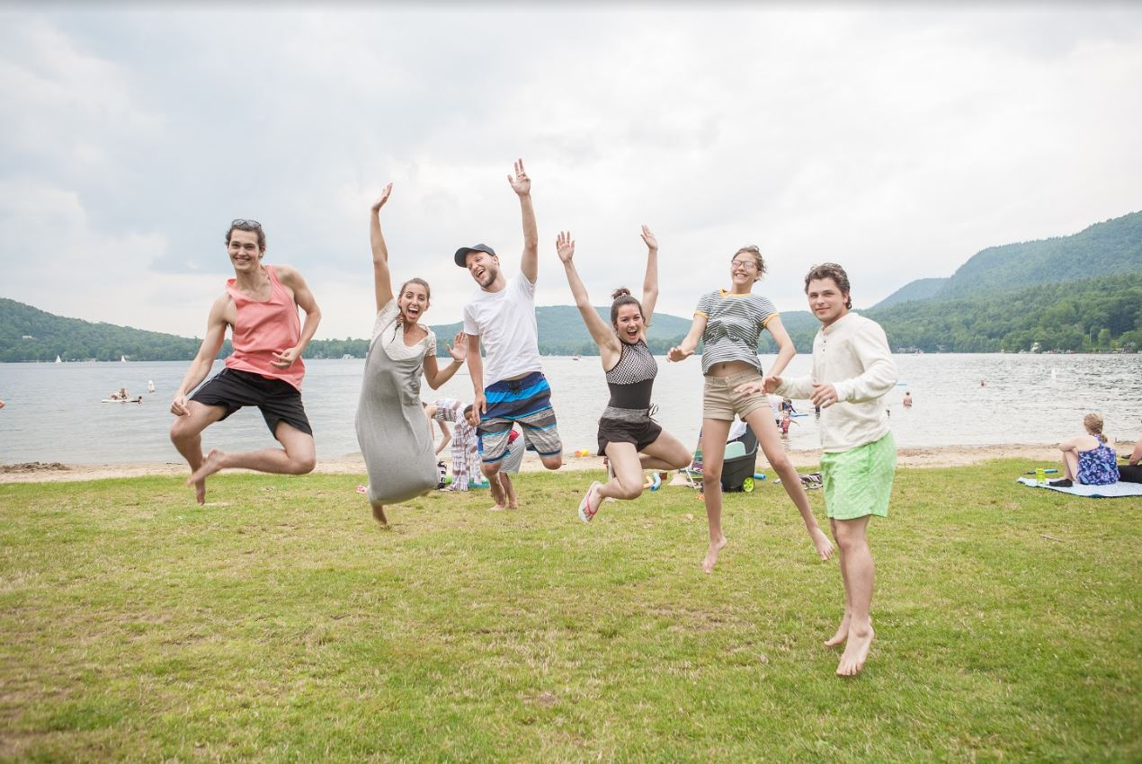 Students jump in front of Lake Dunmore in Vermont.