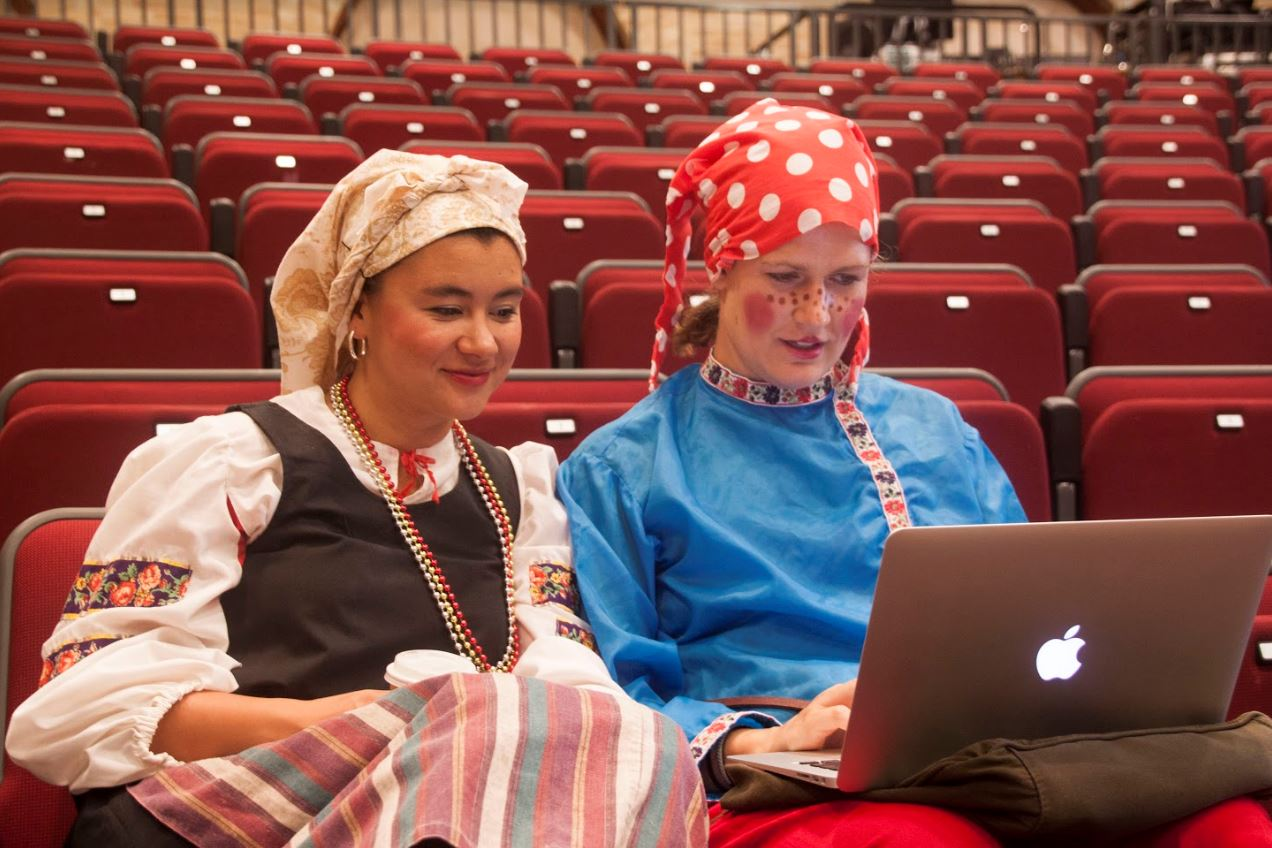 Two girls dresssed up work on their computer.