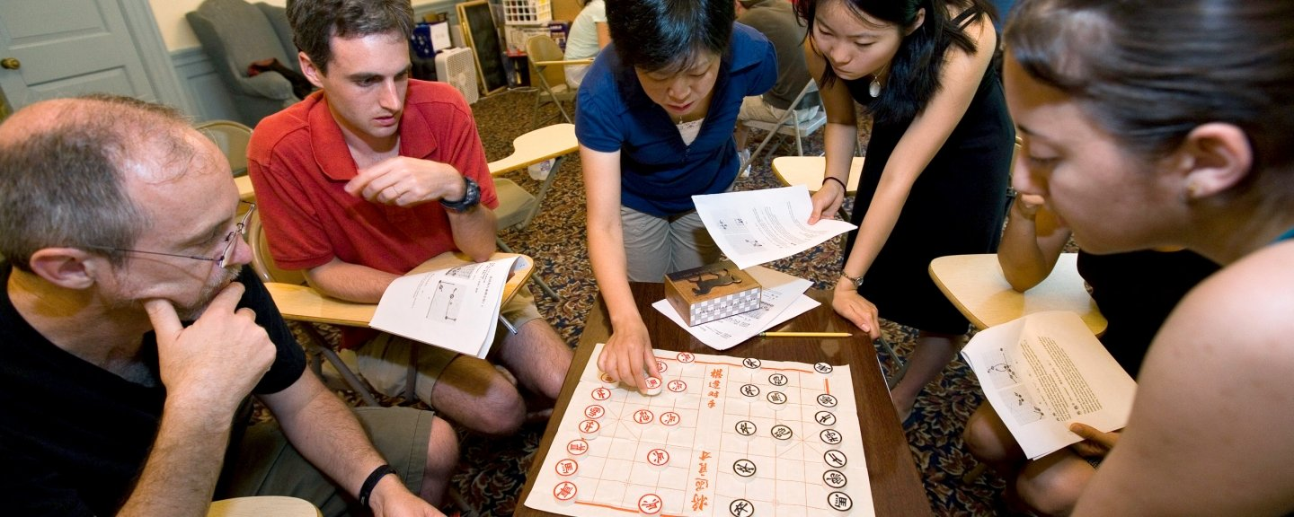 Five students playing a Chinese board game.
