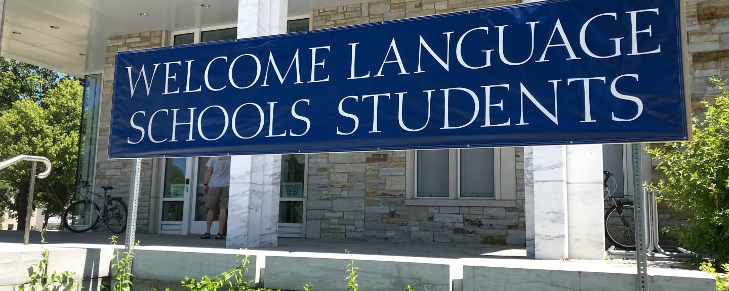 "Banner hanging outside marble building reading ""Welcome Language School Students"""