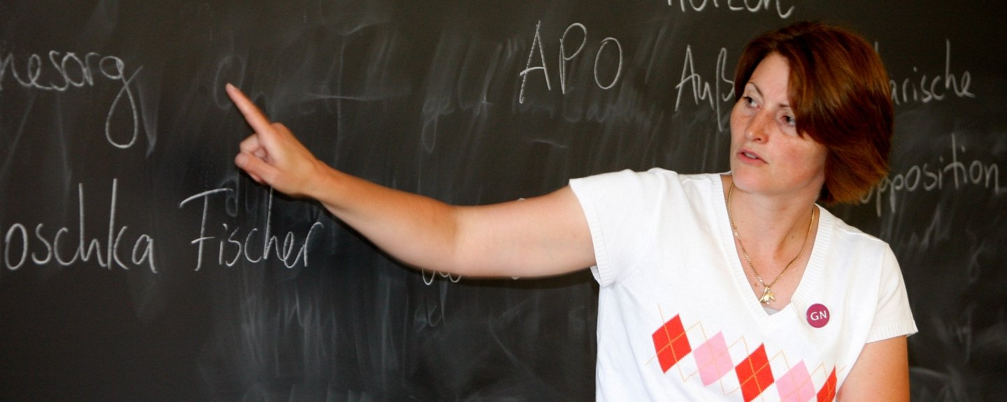 A German professor pointing to words on a chalkboard.