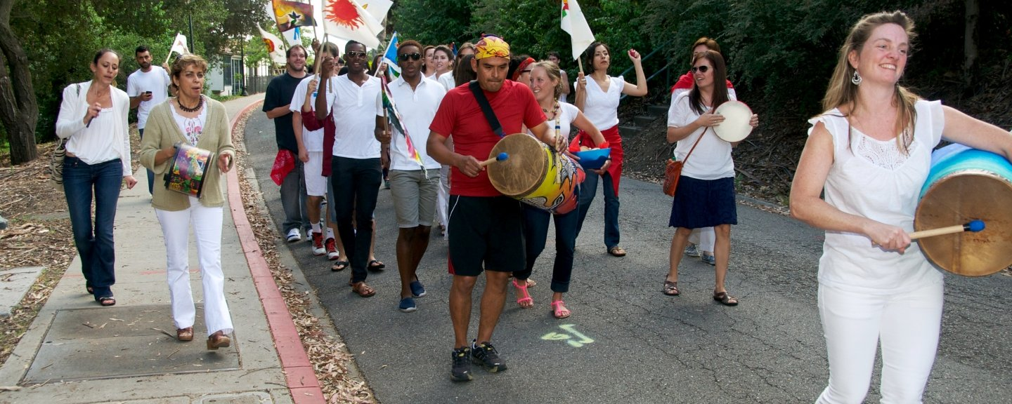 Several adults walking in a parade playing instruments.