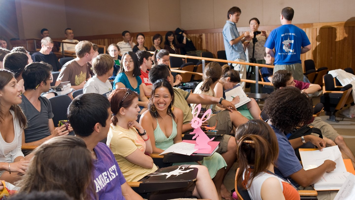 Language School students gather in a lecture hall anticipating the start of class