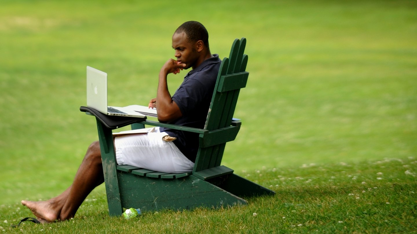 Language Schools student sits in an adirondack chair and reads material on his laptop