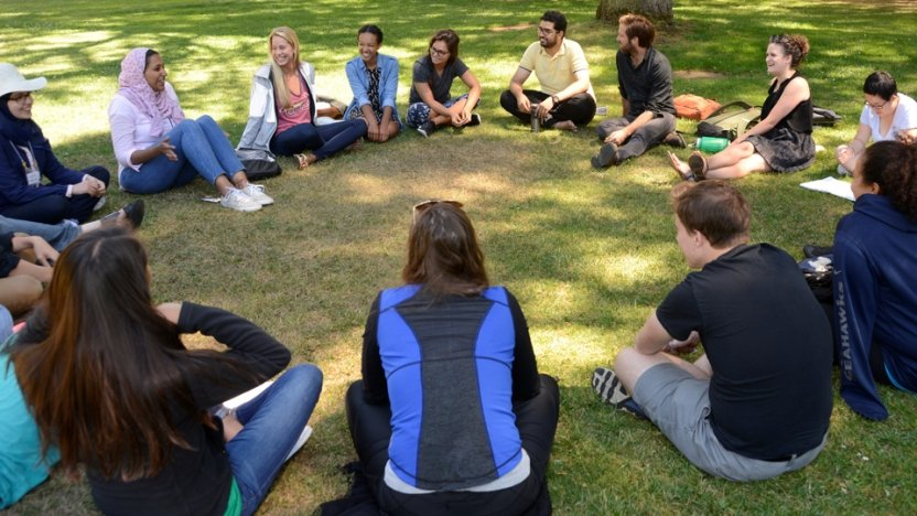 Arabic school students sit outside in grass in circle to communicate in language.