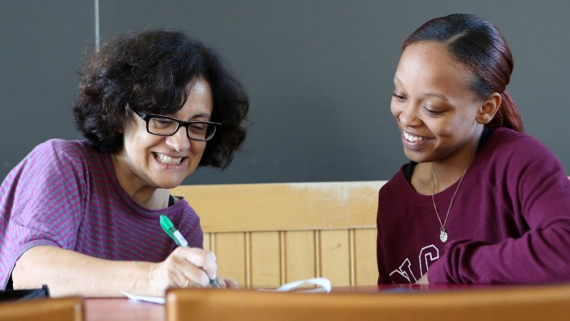 A Spanish language student and her professor work together sitting at a table.