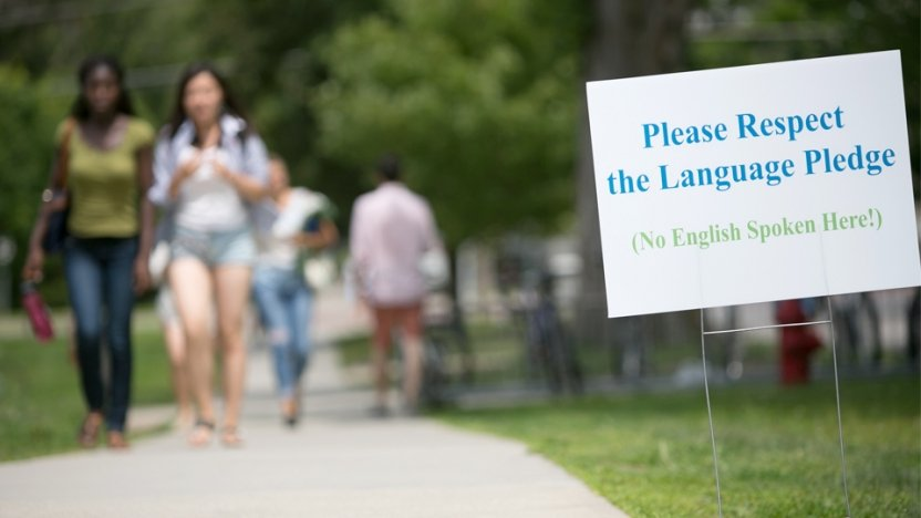 Students walking across campus near Language Pledge sign.