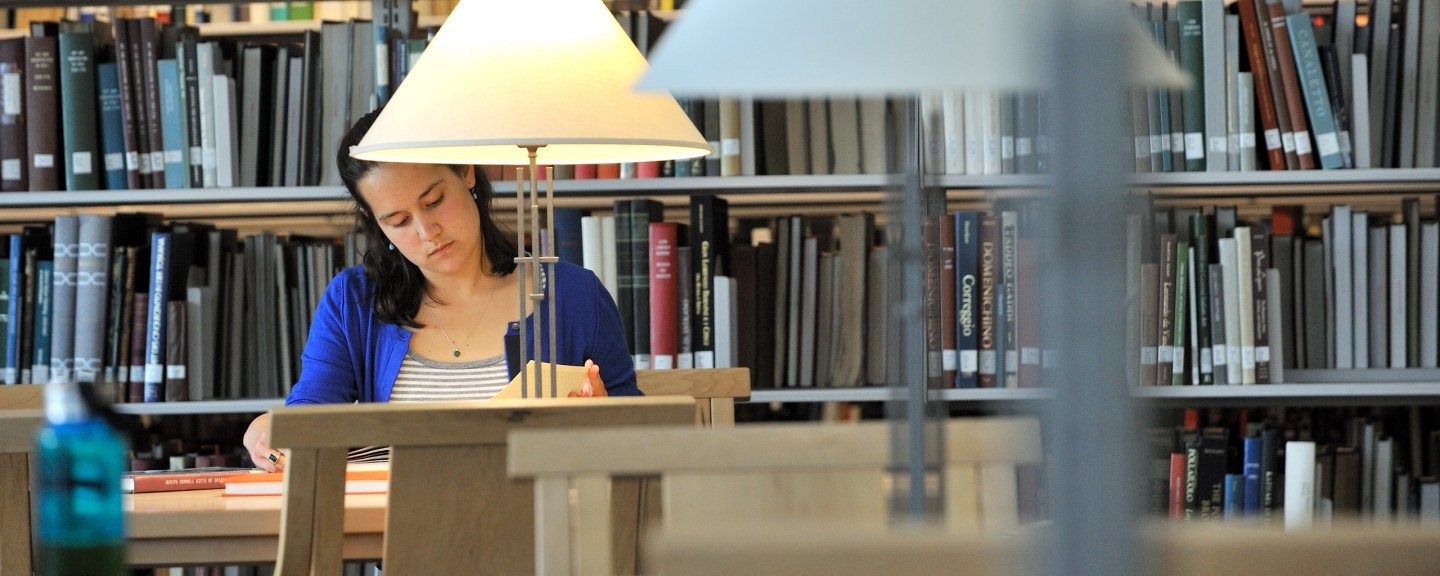 Female student studying at table in library, books in background