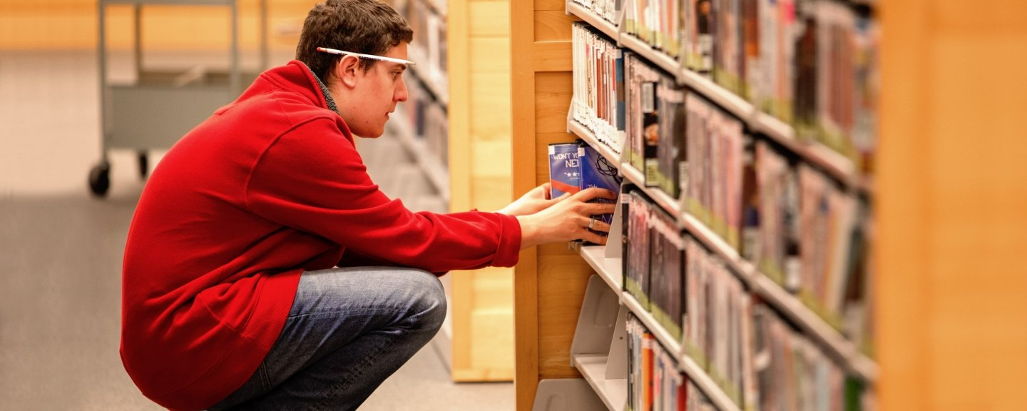 Male student pulling book off shelf in library.