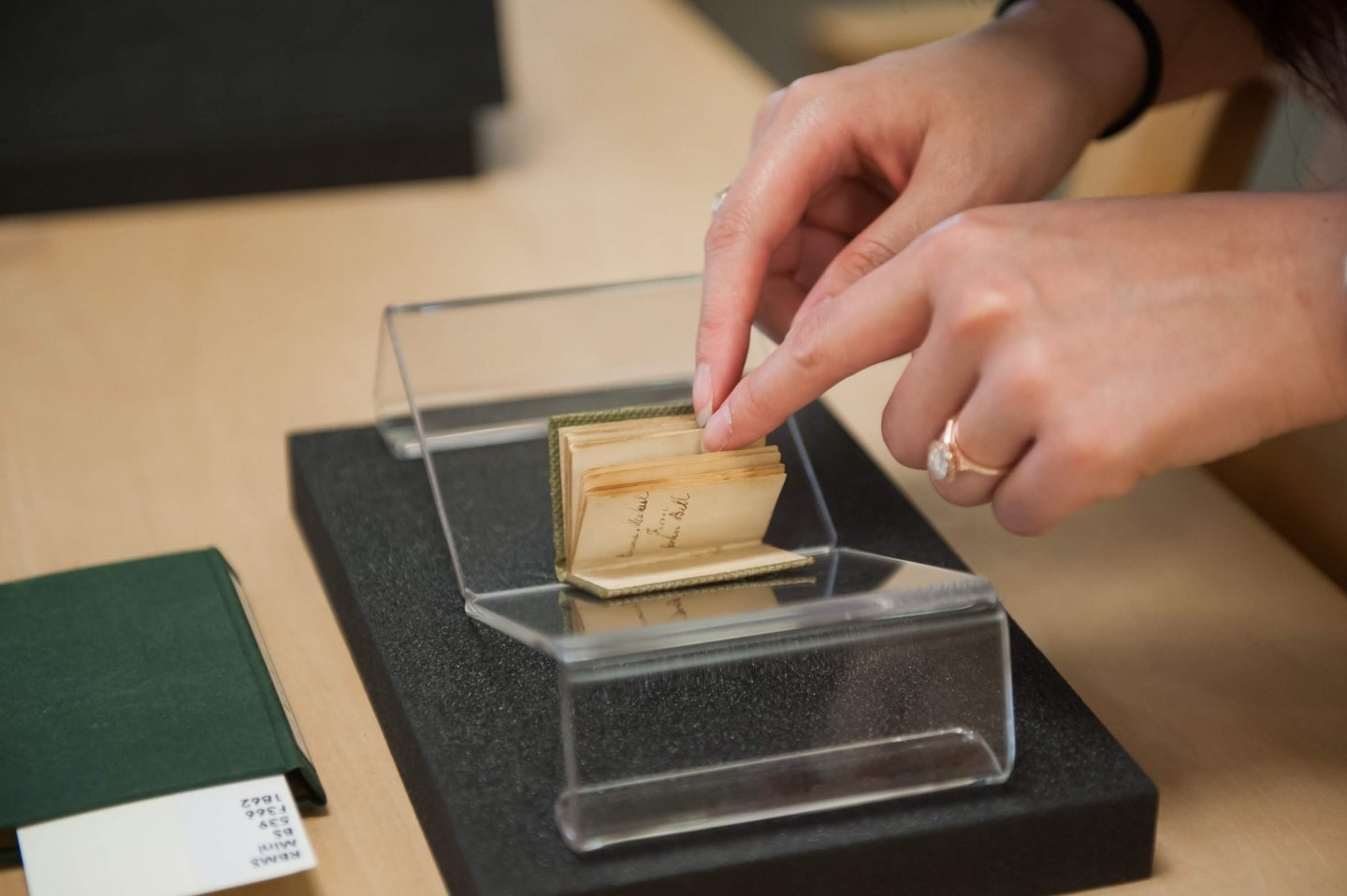 Student holds a tiny book open during Special Collections workshop