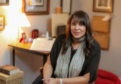 Photograph of Natasha Trethewey, seated at a desk with hands clasped.