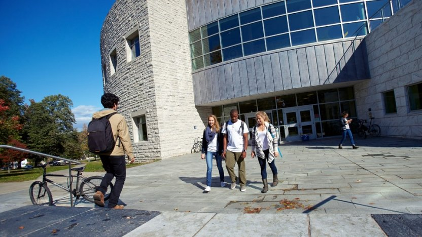 Students walking outside entrance to Davis Library on sunny day.