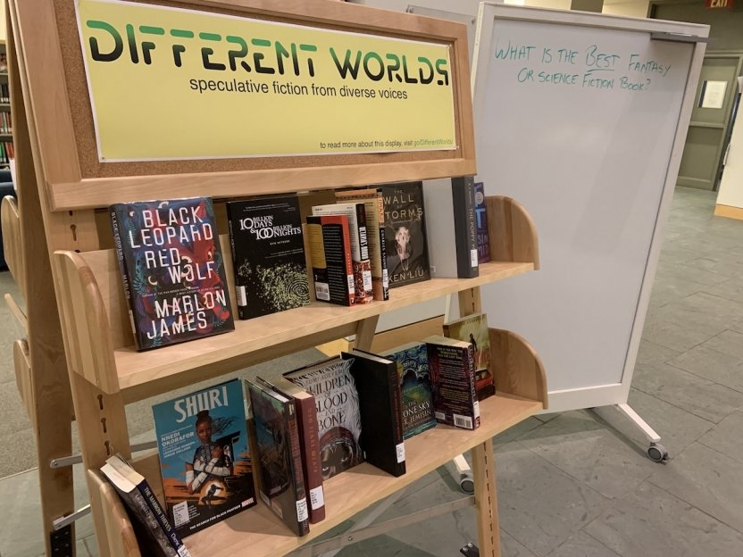 "a picture of books on a book display cart labelled ""Different Worlds: speculative fiction from diverse voices"""