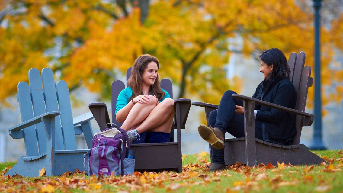 Two students sitting in chairs with the fall foliage in the background