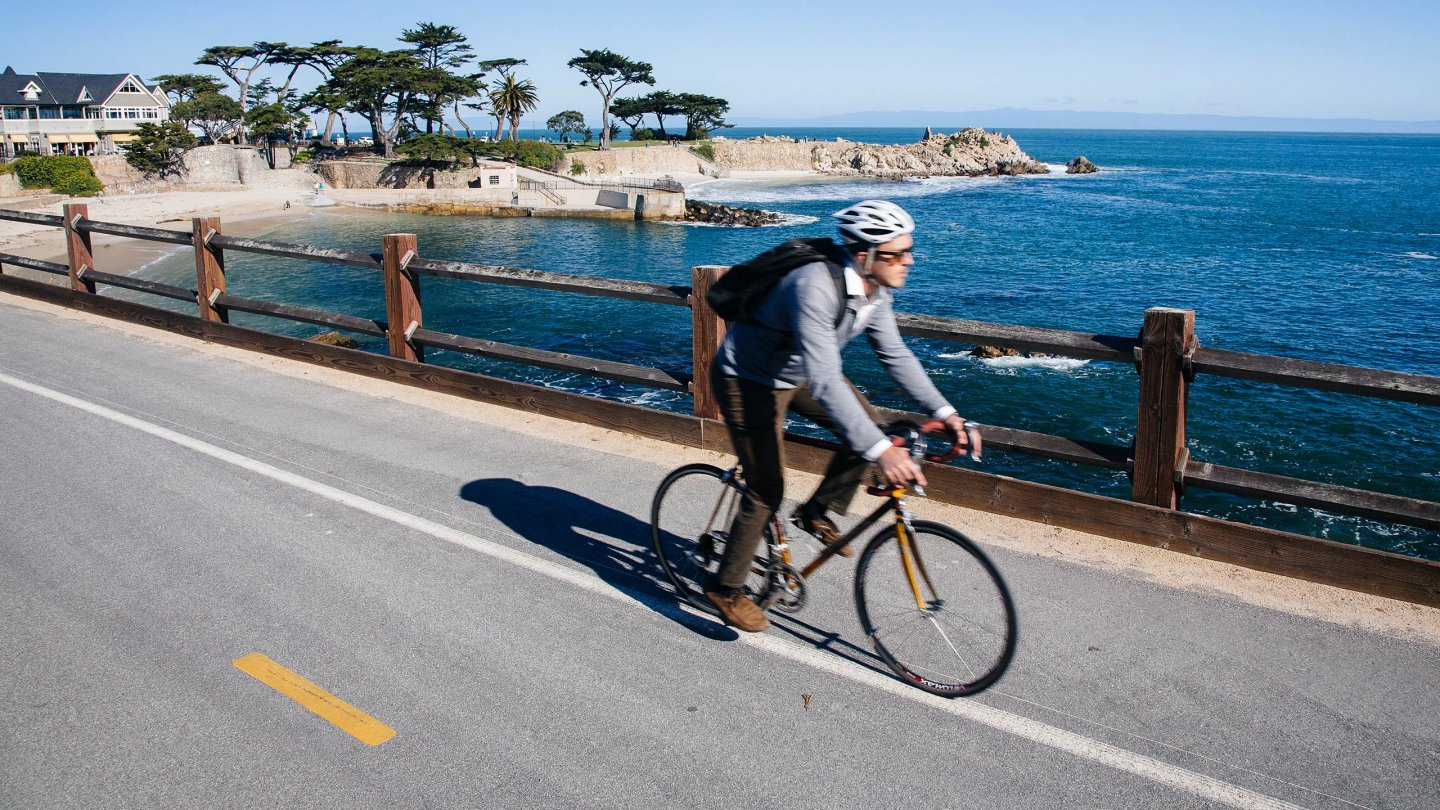Student rides bike along the coast line of Monterey, CA