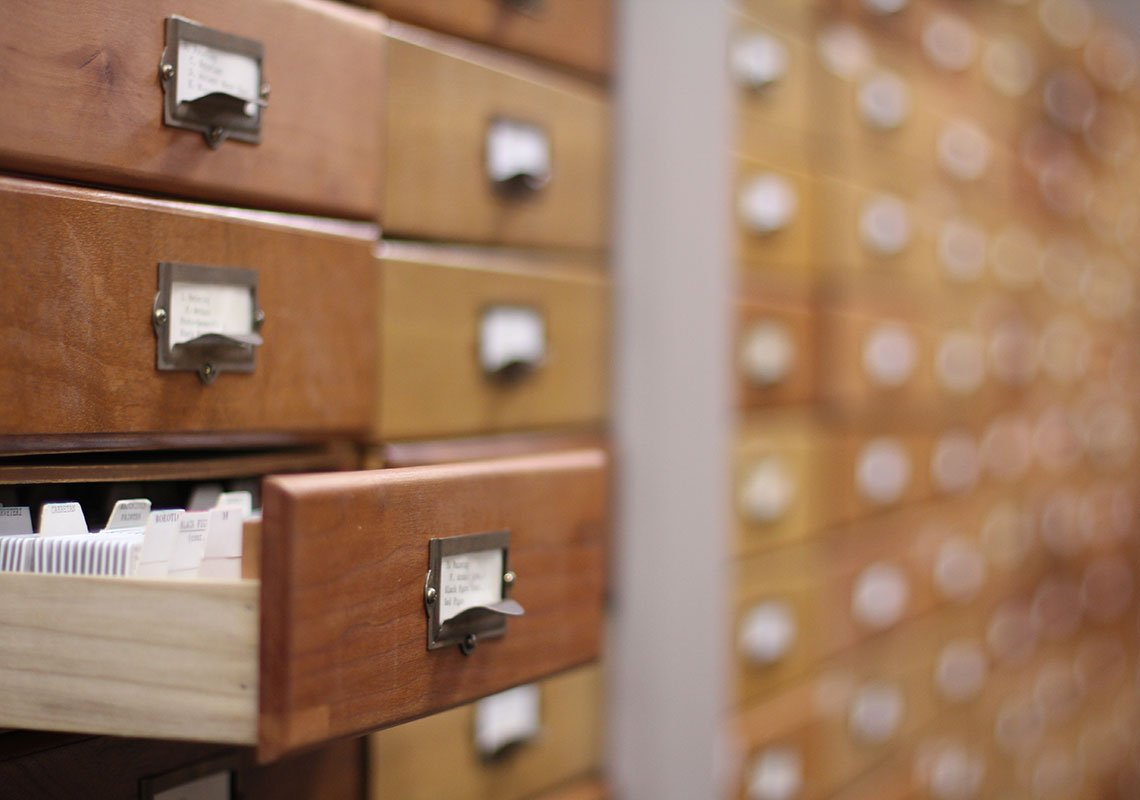 A card catalog with one drawer open.