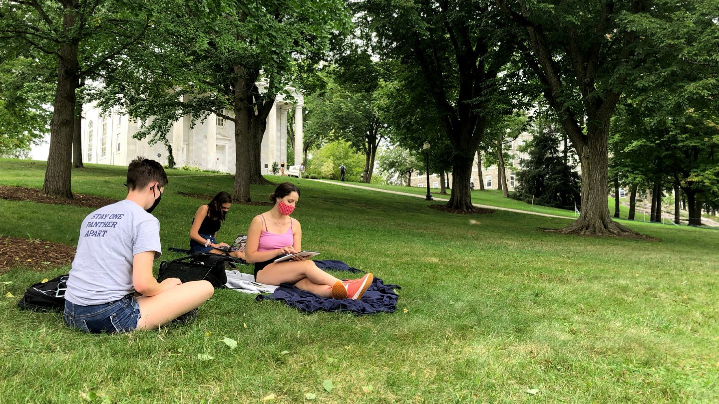 Three Middlebury students sit with masks on lawn and study.
