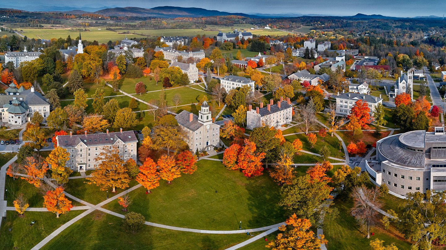 An aerial view of the Vermont campus in fall, with mountains in the distance.