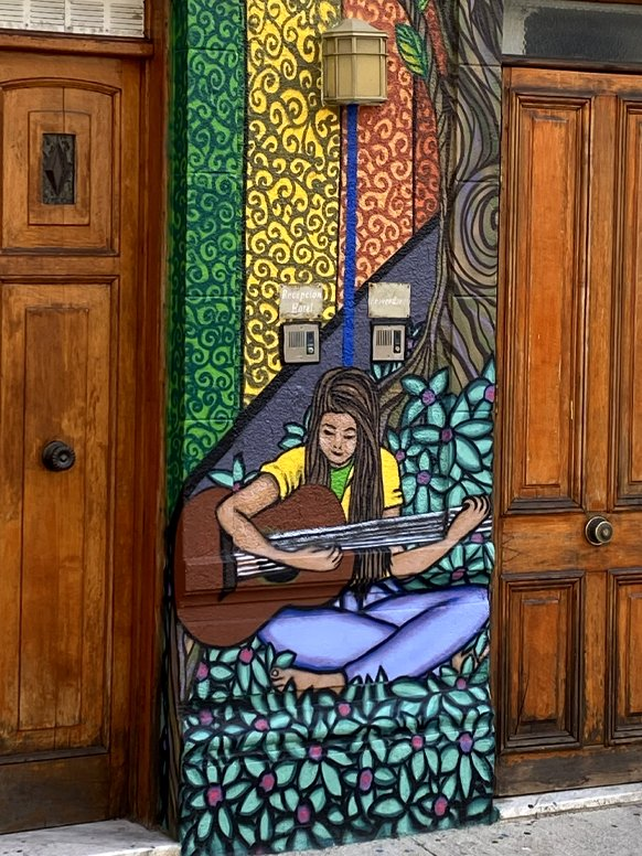 A painted mural of a woman playing guitar on the streets of Chile.