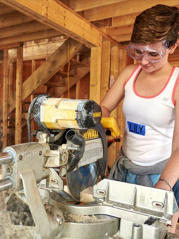 A student works on a home a part of her community service with Habitat for Humanity.
