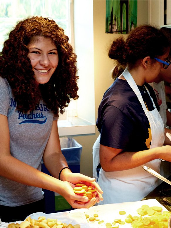 A student works in a local kitchen serving meals to families in need.