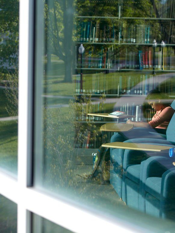 Looking through a window of the Davis library on campus.
