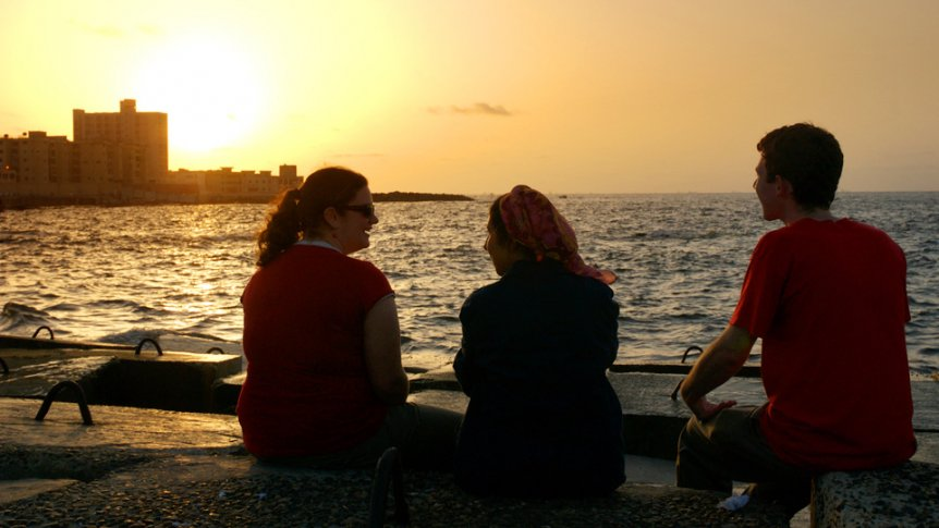 Three students sitting on breakwall near ocean at sunset.