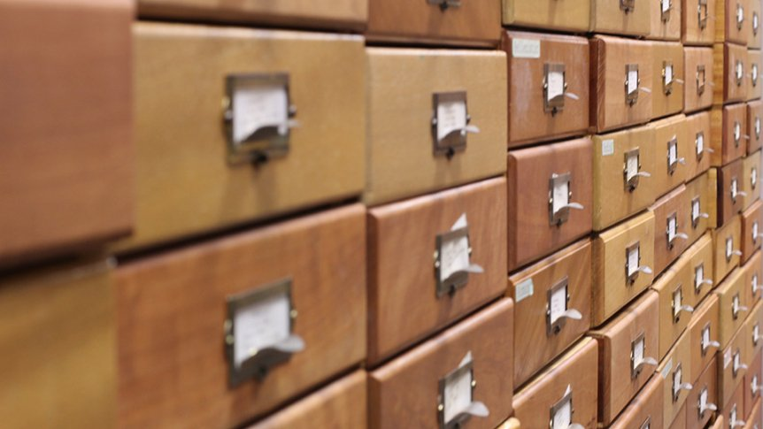 A close-up of an old library index file with wooden drawers.