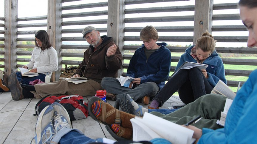 A faculty member meets with students in an outdoor shelter to discuss a nature reading.