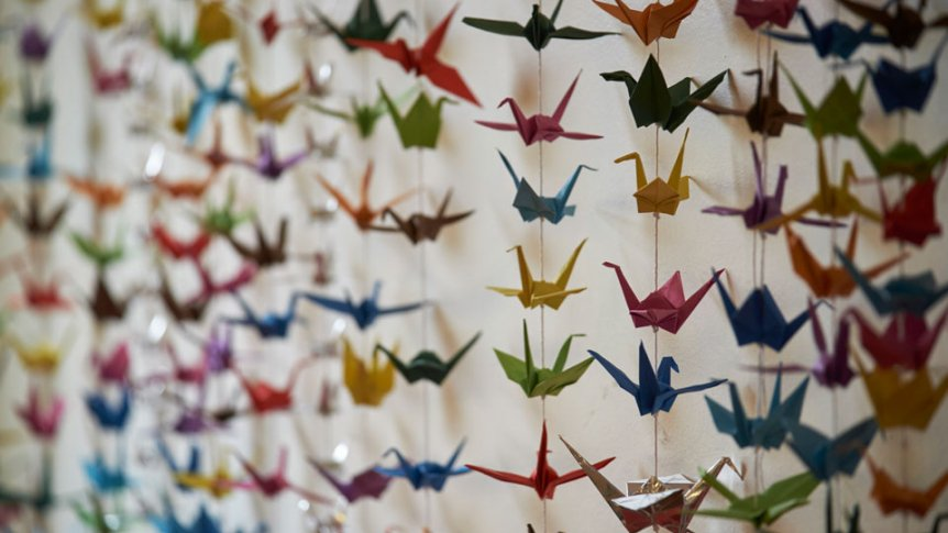 Origami cranes hang in a room.