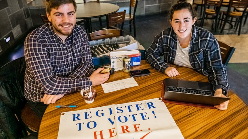 Two Democracy Initiatives participants encourage Middlebury students to register to vote.